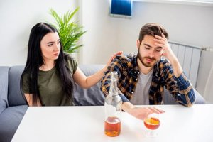 a woman looks concerned as she sees the signs of alcoholism in her significant other